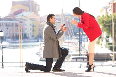 Profile of a proposal of a full body of a fashion elegant couple with a man asking marry to his girlfriend in an idyllic port of an urbanization Stock Photo