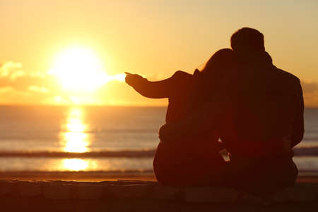Rear view of a couple silhouette sitting cuddling and enjoying pointing at sun at sunset outside on the beach in winter Stock Photo