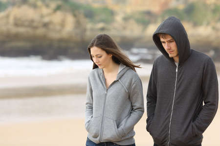 Couple of angry and sad teenagers together walking on the beach Imagens