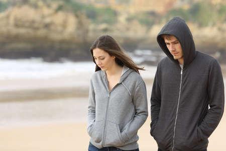 El par de adolescentes enojados y tristes juntos caminando en la playa Foto de archivo - 64330833