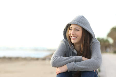 Portret van een gelukkig tienermeisje glimlachen en kijkt naar buiten aan het strand