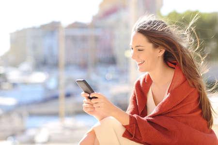 Ragazza che si siede facendo uso di uno Smart Phone che manda un sms ai messaggi in linea in una porta dell'urbanizzazione con il mare nei precedenti e nel vento che muove i suoi capelli Archivio Fotografico