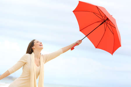 Playful girl joking with a red umbrella on the beach with the sky in the background