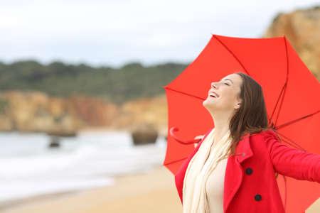 Blije vrouw draagt rode jas inademen van frisse lucht enthousiast met een paraplu op het strand
