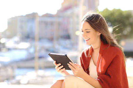e book device: Beautiful woman sitting outdoors and using a tablet watching media content in a sunny windy day in a port of the coast