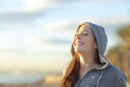Portret van een tiener meisje draagt kap ademhaling diep de frisse lucht op het strand bij zonsopgang in de zomer zonnige dag met een mooie warme lucht op de achtergrond Stockfoto