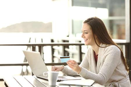 Portrait einer Frau, die auf Linie zu kaufen oder die Buchung von Hotel mit einem Laptop und eine Kreditkarte am Strand in den Ferien. E-Commerce-Konzept