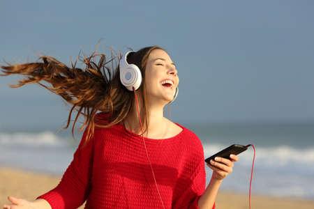 Gelukkig meisje draagt rode kleurrijke trui dansen zingen en luisteren muziek op lijn met de koptelefoon van een slimme telefoon op het strand