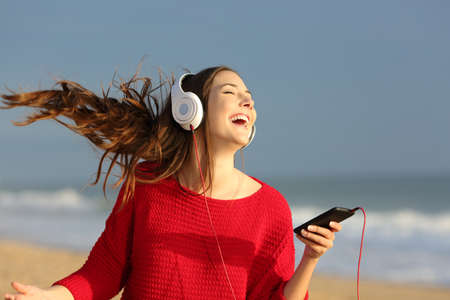 Happy girl wearing red colorful jersey dancing singing and listening music on line with headphones from a smart phone on the beach Banco de Imagens