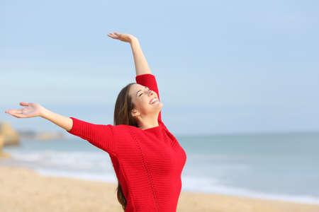 Retrato de una mujer alegre feliz excitado y brazos que crían que llevaba un suéter rojo en la playa en una mañana de sol