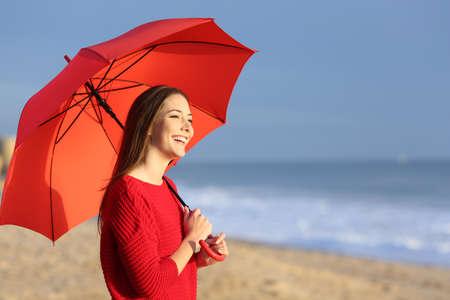 mujer mirando el horizonte: Retrato de una niña feliz con el paraguas rojo en la playa al atardecer con el horizonte y el mar de fondo