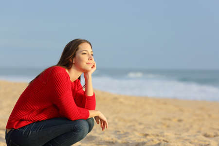 Confiant femme pensive réflexion sur la plage et en regardant à l'horizon au coucher du soleil avec une lumière chaude en arrière-plan