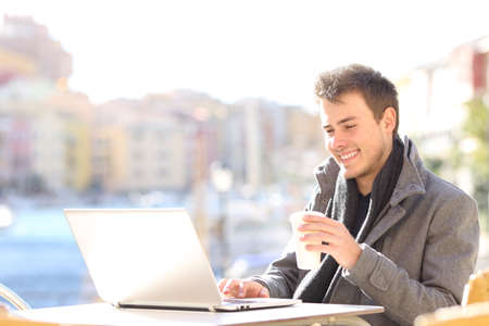 Elegant handsome man using a laptop and searching information on line in a coffee shop terrace of a port with the sea in the background Banco de Imagens