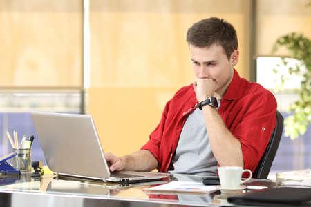 empresario concentrado que trabaja en la línea viendo un ordenador portátil sentado en un escritorio en la oficina