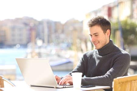 reportero: Retrato de un hombre guapo con la escritura suéter en una computadora portátil en línea en una terraza del bar en un día soleado en un fondo hermoso