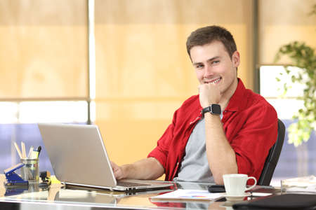 Entrepreneur working at office sitting in a desktop and looking at you