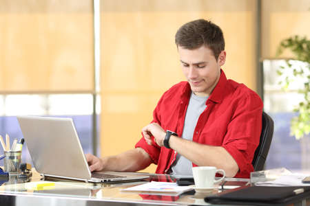 working hours: Businessman working and checking smart watch or clock sitting in a desktop at office