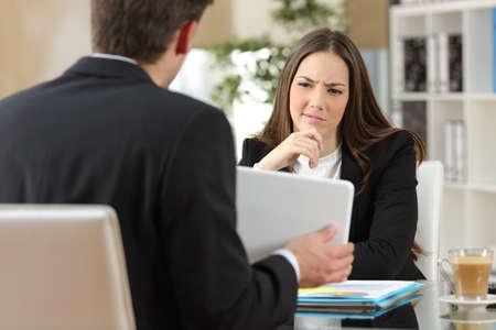 Salesman proberen om een twijfelachtige klant met producten te overtuigen in een tablet op de werkplek