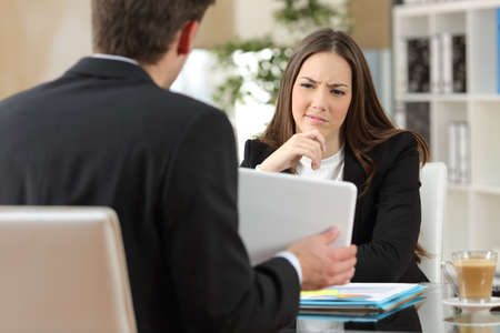 Salesman trying to convince a doubtful customer showing products in a tablet at workplace Standard-Bild