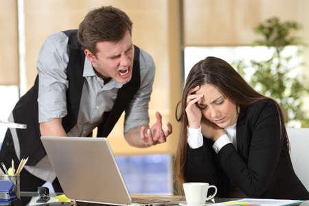 Pesten met een uit de hand baas schreeuwen om een gestresste werknemer in een Desktop op kantoor interieur Stockfoto