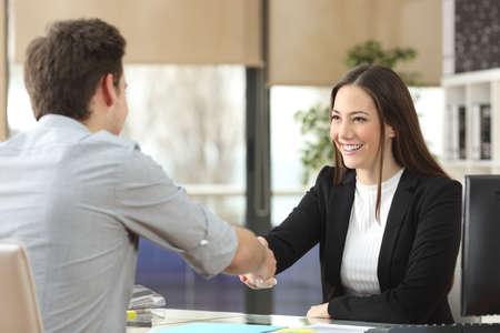 Gelukkig zakenvrouw handshaking met cliënt sluiten deal in een kantoor interieur met een raam op de achtergrond