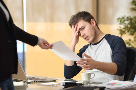 Worried intern receiving a dismiss notification or bad news from his boss or partner sitting in a desktop at office