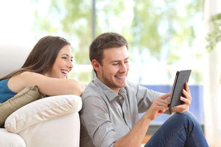 Vrolijk paar met behulp van een tablet op de lijn zit in de woonkamer thuis met een raam op de achtergrond