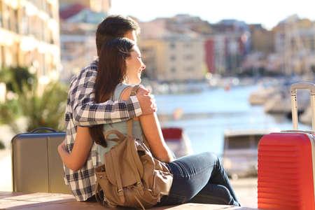 mujer mirando el horizonte: Mayor de turistas sentados y abrazos mientras ve las vacaciones de destino en un puerto con coloridos edificios urbanos en el fondo Foto de archivo