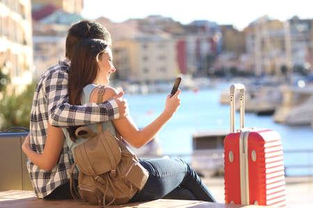 voyage: Couple de touristes assis à la recherche d'information ou réservation d'un hôtel sur un téléphone intelligent sur les vacances Banque d'images