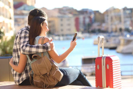 couple laughing: Couple of tourists sitting searching information or booking an hotel on a smart phone on vacations
