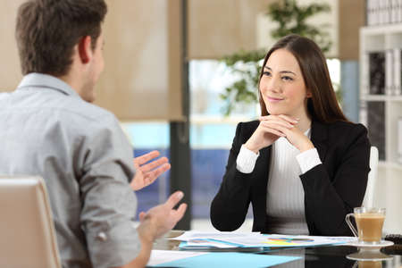 Businesswoman assister à l'écoute d'un client qui parle au bureau Banque d'images