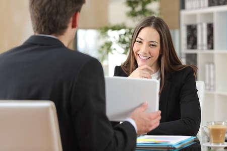 Vendedor que muestra el producto de una tableta a un cliente feliz que está mirando el dispositivo en una oficina de interior