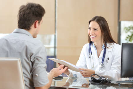Happy doctor female wearing coat attending to her patient in a consultation while is holding a medical history sitting in a desktop Stock Photo