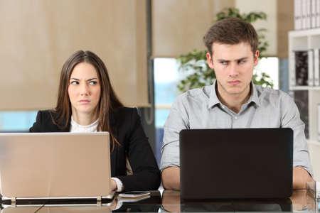 Vista frontale di due uomini d'affari arrabbiati che usano il computer disputano sul posto di lavoro e cercando lateralmente tra loro con invidia