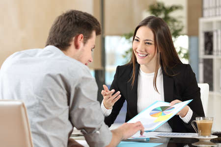 Empresarios sonriendo coworking comentando y mostrando gráfico crecimiento y teniendo una conversación de negocios en el interior de una oficina Foto de archivo