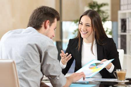 Empresarios sonriendo coworking comentando y mostrando gráfico crecimiento y teniendo una conversación de negocios en el interior de una oficina