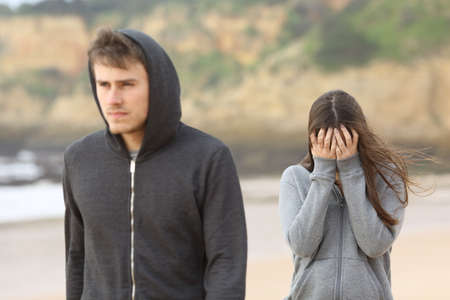 annoyed: Teenager couple breaking up. The angry boyfriend leaves his sad girlfriend
