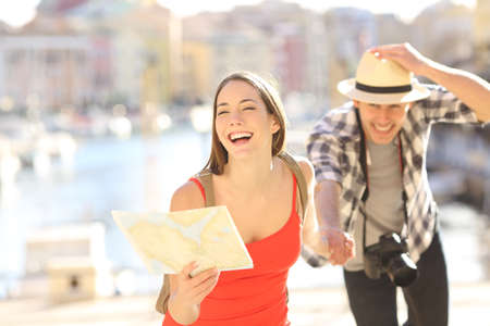 Front view of a happy couple of tourists running towards camera holding a paper map in a travel destination port with the sea in the background. Tourism concept
