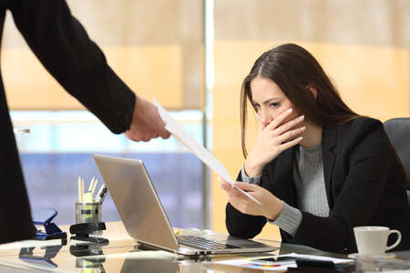 Worried businesswoman receiving a notification from a colleague in her workplace at office Archivio Fotografico