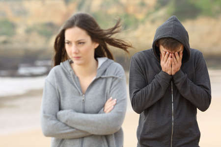 Teenager couple breaking up after argument. The angry girlfriend is rejecting her sad boyfriend
