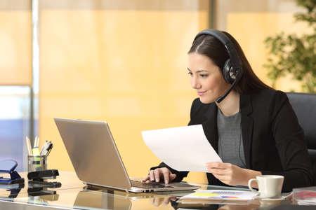프리랜서 운영자가 랩톱 및 헤드셋을 사용하여 온라인으로 작업하고 사무실에서 문서를 들고 있습니다.