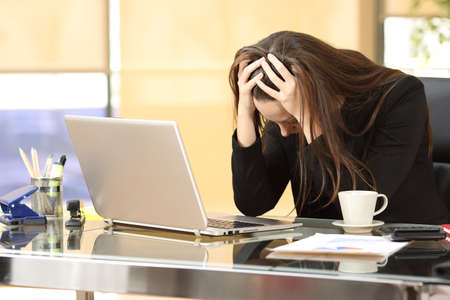 Desperate businesswoman on line worried after bankruptcy in front of a laptop with her hands in the head at office