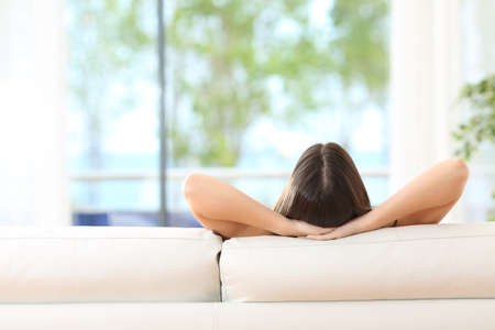 holiday home: Rear view of a woman relaxing sitting on a couch with the hands on the head and looking outdoors through the window of the livingroom at home Stock Photo