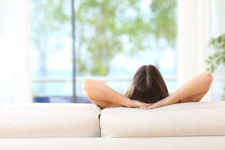 Vue arrière d'une femme de détente assis sur un canapé avec les mains sur la tête et en regardant à l'extérieur à travers la fenêtre de la salle de séjour à la maison