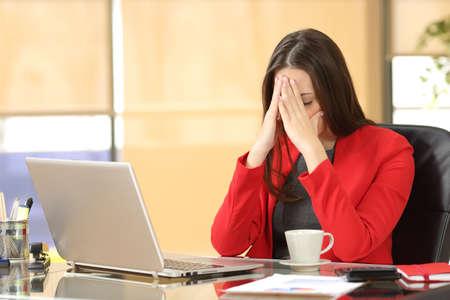 Vermoeide overwerkte onderneemster op kantoor die haar gezicht met handen Stockfoto