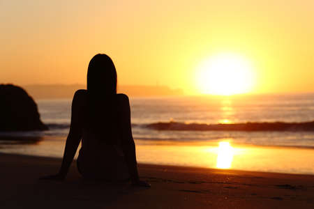 Back view of a woman silhouette sitting on the sand of a beach watching sun at sunrise with the horizon and ocean in the background