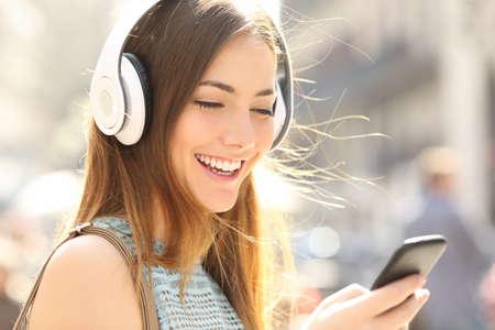 Portret van een gelukkig meisje het luisteren muziek op de lijn met draadloze hoofdtelefoon van een smartphone in de straat in een zonnige zomerdag