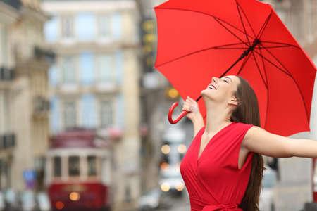 excitación: Retrato de una mujer feliz con blusa roja bajo un paraguas de la respiración en la calle del casco antiguo y en un día de lluvia