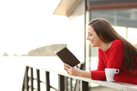 e book device: Side view of happy woman wearing a red sweater reading an ebook in an hotel or apartment on the beach on holidays