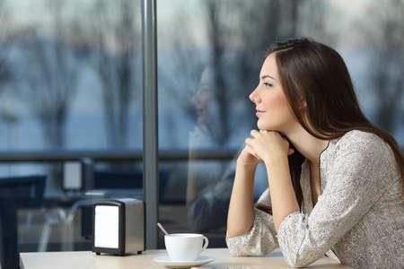 悪い日の窓を通って見、コーヒー ショップで考えて深刻な女性の横顔の肖像画